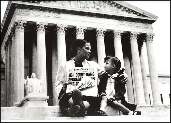 Mrs. Nettie Hunt, sitting on steps of Supreme Court, holding newspaper, explaining to her daughter Nikie the meaning of the Supreme Court's decision banning school segregation.  Courtesy of Library of Congress, Prints and Photographs Division LC-USZ62-127042